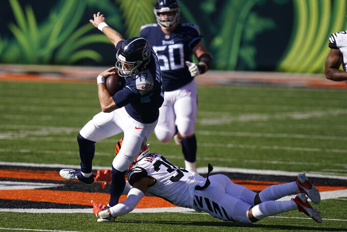 Tennessee Titans quarterback Ryan Tannehill (17) is tackled by Cincinnati Bengals' Jessie Bates (30) during the first half of an NFL football game, Sunday, Nov. 1, 2020, in Cincinnati. (AP Photo/Bryan Woolston)