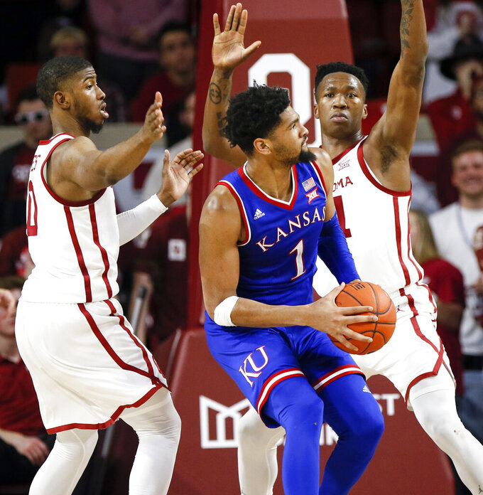 Kansas forward Dedric Lawson, center, tries to get to the basket between Oklahoma guard Christian James, left, and forward Kristian Doolittle, right, in the second half of an NCAA college basketball game in Norman, Okla., Tuesday, March 5, 2019. Oklahoma won 81-68. (AP Photo/Nate Billings)