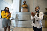 State Rep. London Lamar, left, sings with activist Justin Jones in front of the Nathan Bedford Forrest bust in the State Capitol Thursday, July 22, 2021, in Nashville, Tenn. Jones led protests over the summer of 2020 to have the bust removed. A decadeslong effort to remove the bust of the Confederate general and early Ku Klux Klan leader from the Tennessee Capitol cleared its final hurdle Thursday, with state leaders approving the final vote needed to allow the statue to be relocated to a museum. (George Walker IV/The Tennessean via AP)