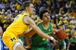 Oregon guard Will Richardson (0) drives on Michigan guard Franz Wagner (21) in the first half of an NCAA college basketball game in Ann Arbor, Mich., Saturday, Dec. 14, 2019. (AP Photo/Paul Sancya)