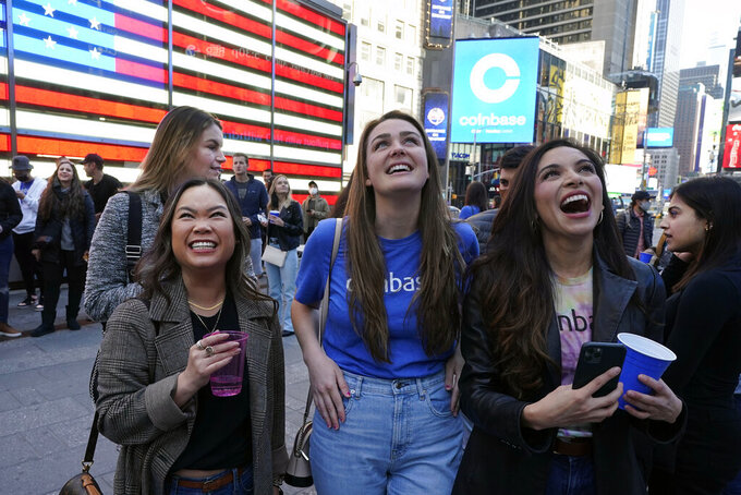 Coinbase employees celebrate outside the Nasdaq MarketSite, in New York's Times Square, Wednesday, April 14, 2021. Wall Street will be focused on Coinbase Wednesday with the digital currency exchange becoming a publicly traded company. (AP Photo/Richard Drew)