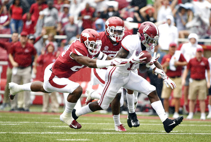 Alabama receiver Henry Ruggs III scoops up a fumble in front of Arkansas defenders Kamren Curl (2) and Dre Greenlaw (23) on his way to scoring a touchdown in the first half of an NCAA college football game Saturday, Oct. 6, 2018, in Fayetteville, Ark. (AP Photo/Michael Woods)