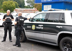 Members of the North Carolina State Highway Patrol talk in a shopping center parking lot in Winston-Salem, N.C., on Wednesday, Sept. 1, 2021. The troopers were part of the law enforcement response after a student was shot and killed at Mount Tabor High School. (AP Photo/Skip Foreman)