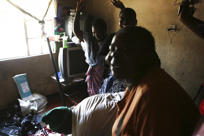 Women celebrate after a baby is delivered in a tiny apartment in the poor surburb of Mbare in Harare, Zimbabwe, Saturday, Nov. 16, 2019, with the help of 72-year old grandmother Esther Zinyoro Gwena. Grandmother Esther Zinyoro Gwena claims to be guided by the holy spirit and has become a local hero, as the country's economic crisis forces closure of medical facilities, and mothers-to-be seek out untrained birth attendants.(AP Photo/Tsvangirayi Mukwazhi)