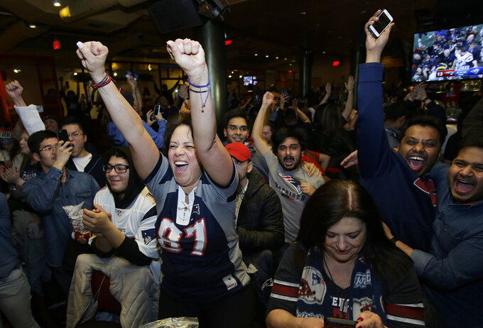 New England Patriots fans celebrate after the Patriots defeated the Los Angeles Rams in the NFL Super Bowl 53 football game in Atlanta at a bar in Boston on Sunday, Feb. 3, 2019. (AP Photo/Steven Senne)