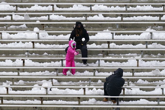 Fans have a snowball fight in Kinnick Stadium before an NCAA college football game between Iowa and Wisconsin, Saturday, Dec. 12, 2020, in Iowa City, Iowa. (AP Photo/Charlie Neibergall)