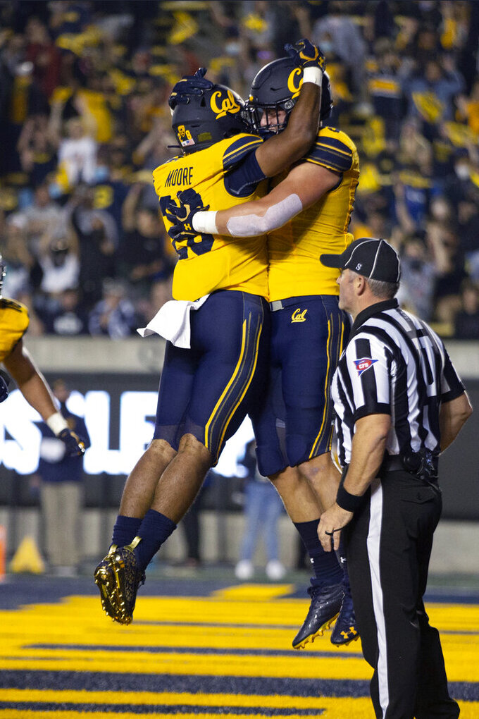California running back Damien Moore (28) and offensive lineman McKade Mettauer (72) celebrate Moore's touchdown run against Nevada during the first quarter of an NCAA college football game Saturday, Sept. 4, 2021, in Berkeley, Calif. (AP Photo/D. Ross Cameron)