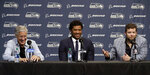 Seattle Seahawks NFL football quarterback Russell Wilson, center, talks to reporters along with head coach Pete Carroll, left, and general manager John Schneider, right, Wednesday, April 17, 2019, in Renton, Wash. Earlier in the week, Wilson signed a $140 million, four-year extension with the team. (AP Photo/Ted S. Warren)