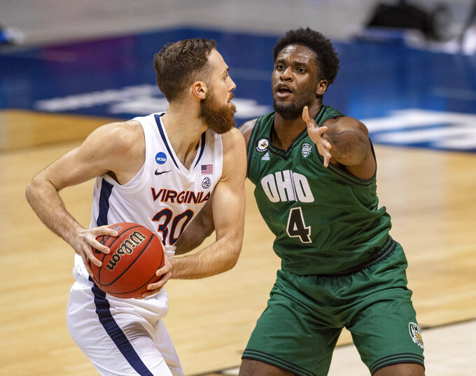Ohio forward Dwight Wilson III (4) defends against Virginia forward Jay Huff (30) during the first half of a first-round game in the NCAA men's college basketball tournament, Saturday, March 20, 2021, at Assembly Hall in Bloomington, Ind. (AP Photo/Doug McSchooler)