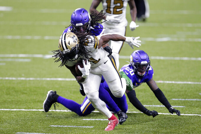 New Orleans Saints running back Alvin Kamara (41) carries against Minnesota Vikings cornerback Jeff Gladney (20) and free safety Anthony Harris in the second half of an NFL football game in New Orleans, Friday, Dec. 25, 2020. (AP Photo/Brett Duke)