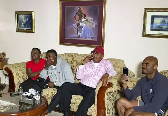 In this still image from video provided by the NFL, Kenneth Murray, second from left, watches the NFL football draft Thursday, April 23, 2020, in Missouri City, Texas. Murray was chosen by the Los Angeles Chargers. (NFL via AP)