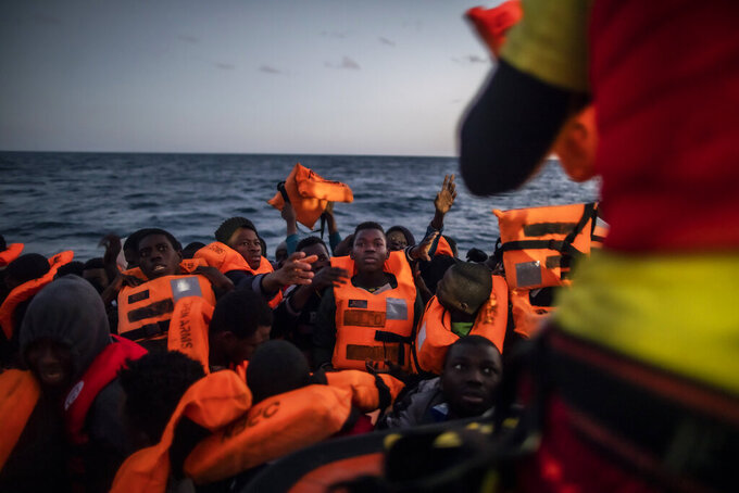 14-year old Bamba Bourahima from Ivory Coast, centre, waits to receive a life vest as rescuer Alberto Agrelo distributes them to all the migrants aboard an overcrowded rubber boat after being rescued by the Spanish NGO Open Arms rescue vessel in the Mediterranean Sea, international waters, at 80 miles off the Libyan coast, Saturday Feb. 13, 2021. Various African migrants drifting in the Mediterranean Sea after fleeing Libya on unseaworthy boats have been rescued. In recent days, the Libyans had already thwarted eight rescue attempts by the Open Arms, a Spanish NGO vessel, harassing and threatening its crew in international waters.(AP Photo/Bruno Thevenin)