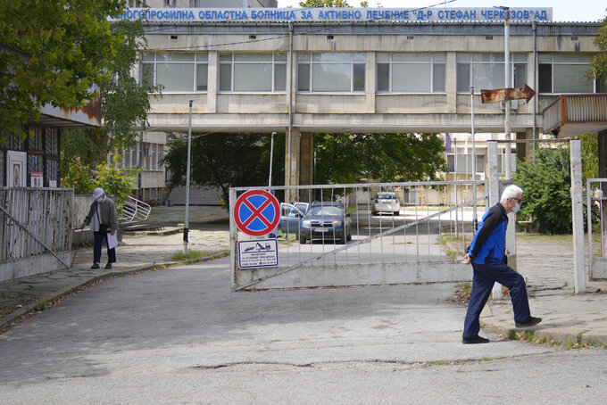 Men walk outside the state hospital in Veliko Tarnovo, Bulgaria, Thursday, Sept. 2, 2021. Despite one of the European Union's highest death rates from COVID-19, and as the country faces a rapid surge of infections due to the Delta variant, people in the Balkan nation are proving the most hesitant in the 27-country bloc to get vaccinated against COVID-19. (AP Photo/Vadim Ghirda)