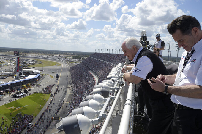 FILE - In this Feb. 22, 2015, file photo, team owner Roger Penske, second from right, watches from the roof of the front grandstands before the Daytona 500 NASCAR Cup Series auto race at Daytona International Speedway in Daytona Beach, Fla. Penske's drivers swept all the races at Indianapolis Motor Speedway and his reward has been induction into the NASCAR Hall of Fame. Penske will be honored Friday night along with Jeff Gordon, deceased drivers Davey Allison and Alan Kulwicki and fellow team owner Jack Roush. (AP Photo/Phelan M. Ebenhack, File)