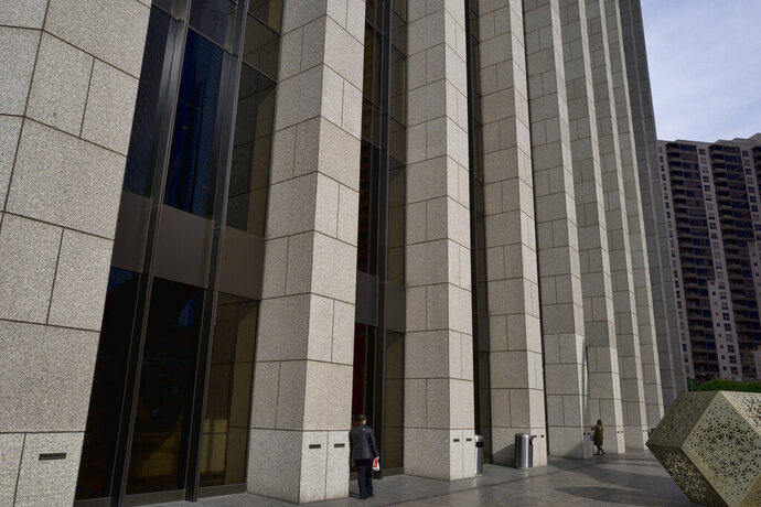 FILE- In this Jan. 8, 2019 photo people are towered by the front facade of the Bank of America Plaza Building in downtown Los Angeles. America's largest companies added women and minorities to their boards of directors at a faster pace over the past two years, a period when sexual harassment scandals thrust workplace equality into the spotlight, according to a study released Wednesday, Jan. 16. (AP Photo/Richard Vogel, File)