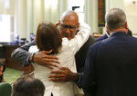 Assemblyman Chris Holden, D-Pasadena, center, is hugged by Assemblywoman Cecilia Aguiar-Curry, D-Winters, after the wildfire measure he co-authored, with Assembly members Autumn Burke, D-Inglewood and Chad Mayes, R-Yucca Valley, was approved by the Assembly in Sacramento, Calif., Thursday, July 11, 2019. The bill, AB1054, aimed at stabilizing the state's electric utilities in the face of devastating wildfires caused by their equipment, was approved overwhelmingly and now goes to the governor. (AP Photo/Rich Pedroncelli)