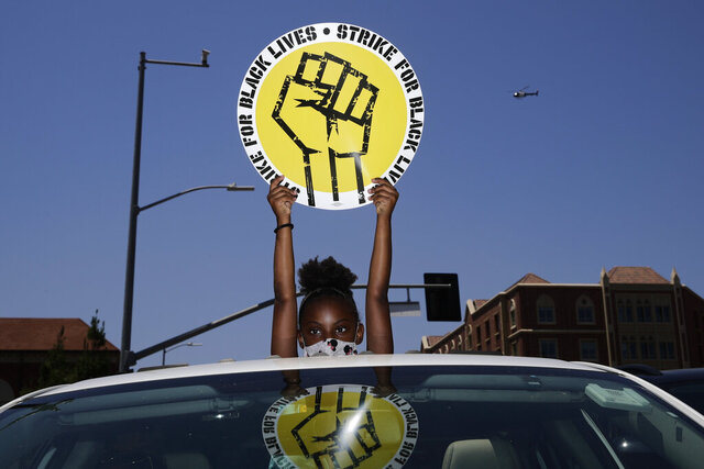 FILE - In this July 20, 2020, file photo, Audrey Reed, 8, holds up a sing through the sunroof of a car during a rally in Los Angeles. Ahead of Labor Day, major U.S. labor unions say they are considering work stoppages in support of the Black Lives Matter movement. (AP Photo/Jae C. Hong, File)