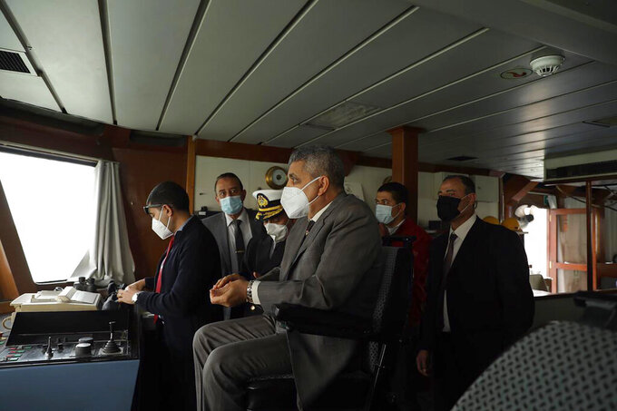 This photo released by the Suez Canal Authority on Thursday, March 25, 2021, shows the head of the Suez Canal Authority, Lt. Gen. Ossama Rabei, center, with a team look from another vessel towards the Ever Given, a Panama-flagged cargo ship, after it become wedged across the Suez Canal. An operation is underway to try to work free the ship, which further imperiled global shipping Thursday as at least 150 other vessels needing to pass through the crucial waterway idled waiting for the obstruction to clear. (Suez Canal Authority via AP)