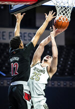 Wake Forest forward Ismael Massoud (25) shoots as Louisville forward JJ Traynor (12) defends during an NCAA college basketball game, Wednesday, Jan. 13, 2021 in Winston-Salem, N.C. (Andrew Dye/The Winston-Salem Journal via AP, Pool)