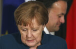 Irish Prime Minister Leo Varadkar in background walks past German Chancellor Angela Merkel as they begin a press following their meeting at Farmleigh House in Dublin, Ireland, Thursday, April 4, 2019. (AP Photo/Peter Morrison)