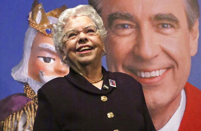 """FILE - Joanne Rogers stands in front of a giant Mister Rogers Forever Stamp following the first-day-of-issue dedication in Pittsburgh on March 23, 2018. Rogers, the widow of Fred Rogers, the gentle TV host who entertained and educated generations of preschoolers on """"Mister Rogers' Neighborhood,"""" has died. She was 92. (AP Photo/Gene J. Puskar, File)"""