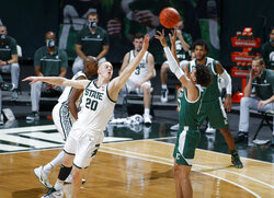 Eastern Michigan's Chris James, right, shoots against Michigan State's Joey Hauser (20) during the first half of an NCAA college basketball game Wednesday, Nov. 25, 2020, in East Lansing, Mich. (AP Photo/Al Goldis)