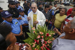 Father Edwin Roman attempts to convince the police to allow relatives of imprisoned and dead anti-government demonstrators to enter the San Miguel Arcangel Church in Masaya, Nicaragua, Thursday, Nov. 14, 2019. The relatives have started a hunger strike to demand the freedom of their relatives, jailed for protesting against the government of President Daniel Ortega. (AP Photo/Alfredo Zuniga)