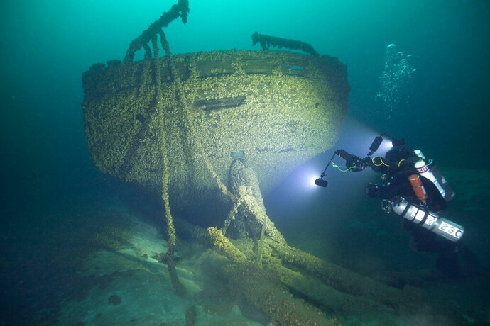 In this Aug. 24, 2019, photo provided by John Janzen, diver John Scoles maneuvers around the wreckage of the schooners Peshtigo and St. Andrews, lost in 1878 near Beaver Island in northern Lake Michigan. A group of maritime history enthusiasts led by Boyne City, Michigan diver and explorer, Bernie Hellstrom have announced the discovery of the schooners. The site was located in 2010 by Hellstrom during one of his many trips to explore the Beaver Island archipelago. (John Janzen via AP)