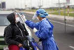 A nurse from the Ministry of Public Health takes a sample from a person on a motorcycle, at a new coronavirus mobile test site in Asuncion, Paraguay, Wednesday, April 8, 2020. The government of Paraguay has announced the extension of the quarantine for one week until April 21. (AP Photo/Jorge Saenz)