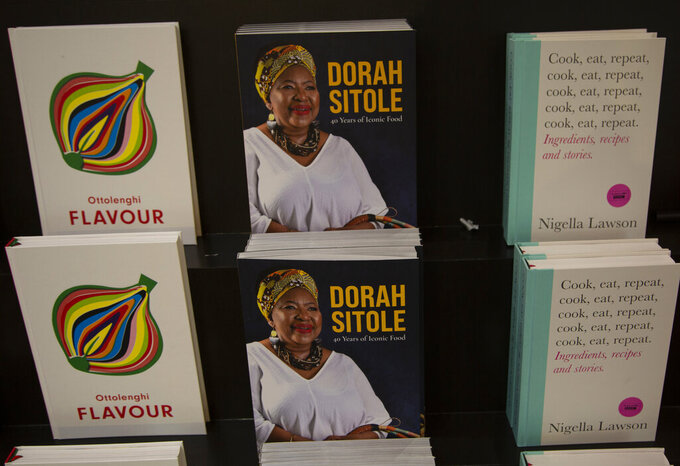 "Copies of Dorah Sitole's cook book ""40 Years of Iconic Food"", seen at centre, in Exclusive Books in Hyde Park Corner, Johannesburg, Tuesday, Jan. 12, 2021.  South Africa's pioneer Black food writer Sitole, portrait on cover, who quietly defied apartheid to win respect and a readership for African cuisine, died of COVID-19, in  Jan. 2021. (AP Photo/Denis Farrell)"
