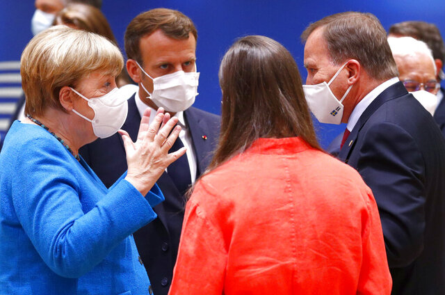 German Chancellor Angela Merkel, left, speaks with French President Emmanuel Macron, second left, Finland's Prime Minister Sanna Marin, second right, and Sweden's Prime Minister Stefan Lofven, right, during a round table meeting at an EU summit in Brussels, Saturday, July 18, 2020. Leaders from 27 European Union nations meet face-to-face for a second day of an EU summit to assess an overall budget and recovery package spread over seven years estimated at some 1.75 trillion to 1.85 trillion euros. (Francois Lenoir, Pool Photo via AP)