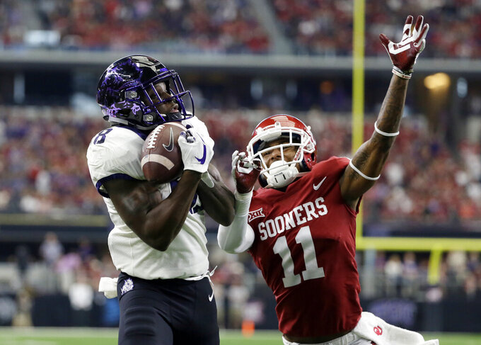 FILE - In this Saturday, Dec. 2, 2017 file photo, TCU wide receiver Jalen Reagor (18) catches a touchdown pass in front to Oklahoma cornerback Parnell Motley (11) in the first half of the Big 12 Conference championship NCAA college football game in Arlington, Texas. Major improvements on defense have pushed Oklahoma and Baylor into the Big 12 championship game. Oklahoma led the Big 12 in total defense during conference play after finishing last a season ago. Baylor led the Big 12 in scoring defense and ranked third in total defense in league play a year after finishing seventh in total defense and eighth in scoring defense. (AP Photo/Tony Gutierrez, File)