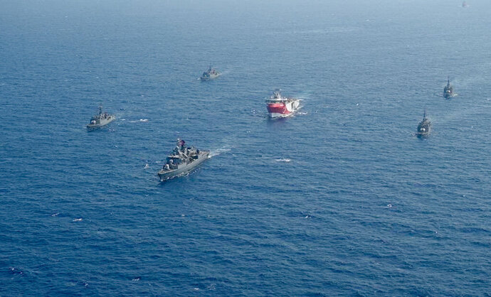 In this taken Monday, Aug. 10, 2020, Turkey's research vessel, Oruc Reis, center, is surrounded by Turkish navy vessels as it was heading in the west of Antalya on the Mediterranean, Turkey.  Tension remains high between Greece and Turkey, whose warships are in the eastern Mediterranean where Turkey has sent a research vessel to carry out seismic research for energy resources in an area Greece says is on its continental shelf. (IHA via AP)