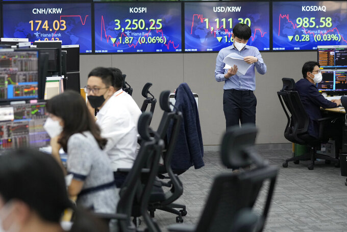 A currency trader takes a look at documents at the foreign exchange dealing room of the KEB Hana Bank headquarters in Seoul, South Korea, Tuesday, June 8, 2021. Stocks edged lower in Asia on Tuesday after a mixed finish on Wall Street, as investors weighed the risks of inflation against signs the recovery from the pandemic is gaining momentum. (AP Photo/Ahn Young-joon)