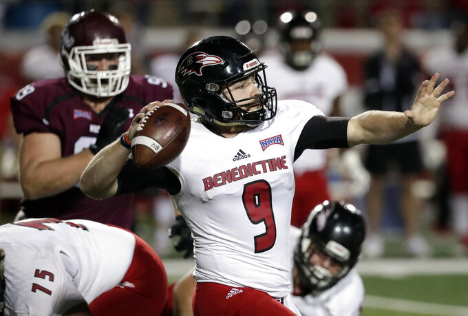 Benedictine quarterback Shaefer Schuetz (9) throws a pass as he is pressured by Morningside defensive lineman Alex Paulson, back left, during the first half of an NAIA Championship college football game, Saturday, Dec. 15, 2018, in Daytona Beach, Fla. (AP Photo/John Raoux)