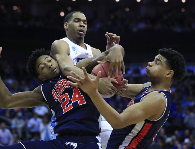 North Carolina's Garrison Brooks, center, reaches for a rebound between Auburn's Anfernee McLemore (24) and Chuma Okeke during the second half of a men's NCAA tournament college basketball Midwest Regional semifinal game Friday, March 29, 2019, in Kansas City, Mo. (AP Photo/Orlin Wagner)