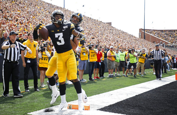 Iowa wide receiver Tyrone Tracy, left, celebrates his touchdown reception with Iowa tight end Nate Wieting, right, during the first half of an NCAA college football game against Rutgers, Saturday, Sept. 7, 2019, in Iowa City. (AP Photo/Matthew Putney)
