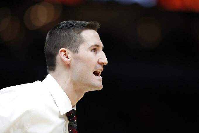 Southern Illinois head coach Bryan Mullins is seen on the sidelines during the first half of an NCAA college basketball game against Bradley in the quarterfinal round of the Missouri Valley Conference men's tournament Friday, March 6, 2020, in St. Louis. (AP Photo/Jeff Roberson)