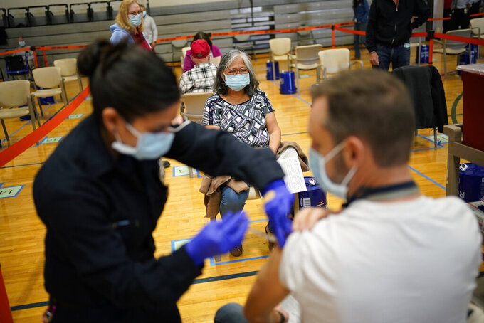FILE - In this Feb. 17, 2021, file photo, people receive the COVID-19 vaccine at a vaccination site in Las Vegas. Coronavirus management officials acknowledged Wednesday, March 10, 2021, that some vaccination appointment slots are going unused in Las Vegas, and that more doses are available than are being administered at the area's two largest mass vaccination sites. (AP Photo/John Locher, File)