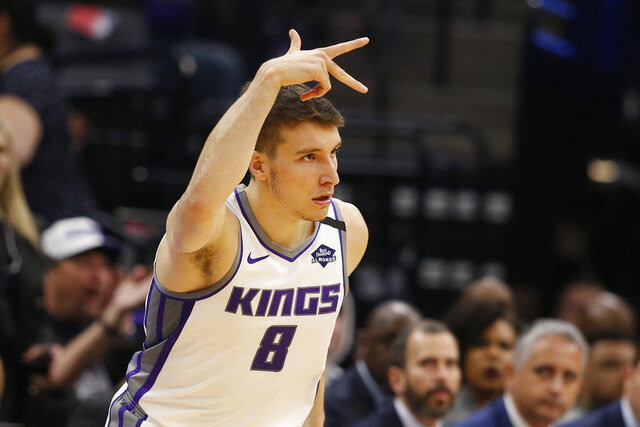 Sacramento Kings guard Bogdan Bogdanovic flashes three fingers after scoring a 3-point basket during the first quarter of the team's NBA basketball game against the Washington Wizards in Sacramento, Calif., Tuesday, March 3, 2020. (AP Photo/Rich Pedroncelli)