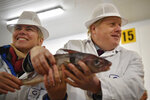 Britain's Prime Minister and Conservative Party leader Boris Johnson, right, visits Grimsby fish market in Grimsby, northeast England, Monday Dec. 9, 2019, ahead of the general election on Dec. 12. All 650 seats in the House of Commons are up for grabs Thursday when voters will pass judgement on a divisive election that will determine Britain's future with European Union. (Ben Stansall/Pool via AP)