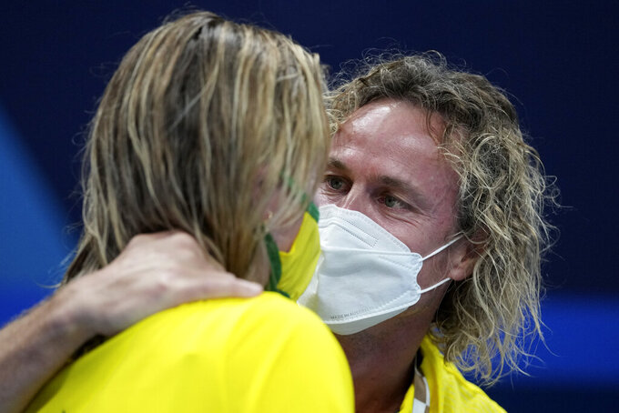 Ariarne Titmus of Australia is embraced by her coach Dean Boxall after winning the women's 200-meter freestyle final at the 2020 Summer Olympics, Wednesday, July 28, 2021, in Tokyo, Japan. (AP Photo/Matthias Schrader)