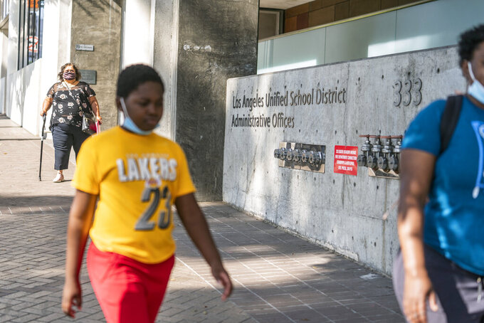 Students walk outside the Los Angeles Unified School District headquarters building in Los Angeles Thursday, Sept. 9, 2021. The Los Angeles board of education is expected to vote Thursday, on whether to require all students 12 and older to be fully vaccinated against the coronavirus to participate in on-campus instruction in the nation's second-largest school district. (AP Photo/Damian Dovarganes)