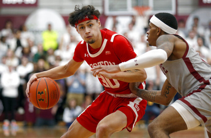 Boston University's Javante McCoy, left, drives past Colgate's Nelly Cummings, right, in the first half of the NCAA Patriot League Conference basketball  championship at Cotterell Court, Wednesday, March 11, 2020, in Hamilton, N.Y. (AP Photo/John Munson)