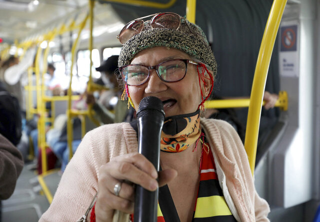 "Marlene Alfonso, a 69-year-old Venezuelan grandmother who goes by ""Toothless Cindy,"" sings about Venezuelan migrants' lives in hopes of tips from commuters on the Transmilenio, the crowded and crime-ridden public bus system in Bogota, Colombia, Tuesday, Nov. 3, 2020. ""I'm showing people how to not feel defeated,"" Alfonso said after finishing a set of songs. (AP Photo/Fernando Vergara)"