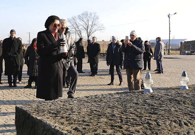 In this image provided by the US Consulate General in Krakow, U.S. House Speaker Nancy Pelosi places a memorial light on the monument to some 1.1 million victims of the World War II Nazi death camp of Auschwitz-Birkenau during a visit to the site of the former camp just days before the 75th anniversary of its 1945 liberation by the Soviet troops, at the Auschwitz-Birkenau Museum, in southern Poland, on Tuesday, Jan. 21, 2020. (US Consulate General in Krakow via AP)