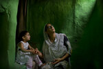 """In this Sept. 27, 2019, photo, Sumaira Bilal, wife of Kashmiri detainee Bilal Ahmed, talks to her two-year-old daughter as they sit for photographs on a staircase of their house in Srinagar, Indian controlled Kashmir. Ahmed was detained on the night of Aug. 5, the day Indian Prime Minister Narendra Modi's Hindu-nationalist government repealed Article 370 of the Indian Constitution, stripping Kashmir of its statehood. Sumaira says her daughter points to the window often and calls for her father """"Baba, Baba, when are you coming back?"""" (AP Photo/ Dar Yasin)"""