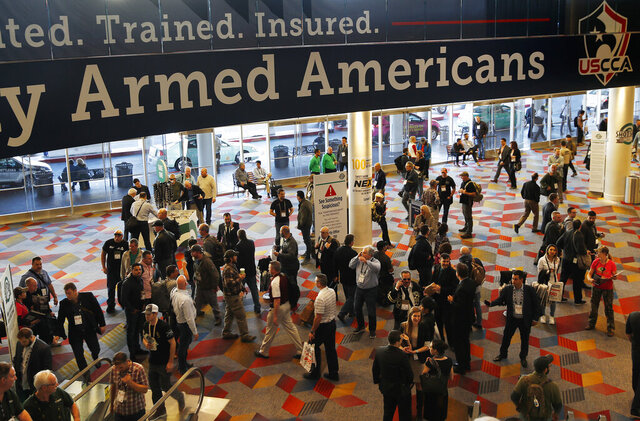 FILE - In this Wednesday, Jan. 24, 2018, file photo, people walk through the hall outside of the SHOT Show gun show in Las Vegas. The gun industry is gathering for its annual conference, in January 2020, amid a host of uncertainty: slumping gun sales, a public increasingly agitating for restrictions on access to firearms and a presidential campaign that threatens gun rights like perhaps no other time in modern American history. (AP Photo/John Locher, File)