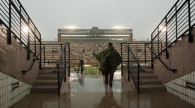 A lone fan runs into Memorial Stadium during a rain shower before the start of the Arkansas-Missouri NCAA college football game Friday, Nov. 23, 2018, in Columbia, Mo. (AP Photo/L.G. Patterson)