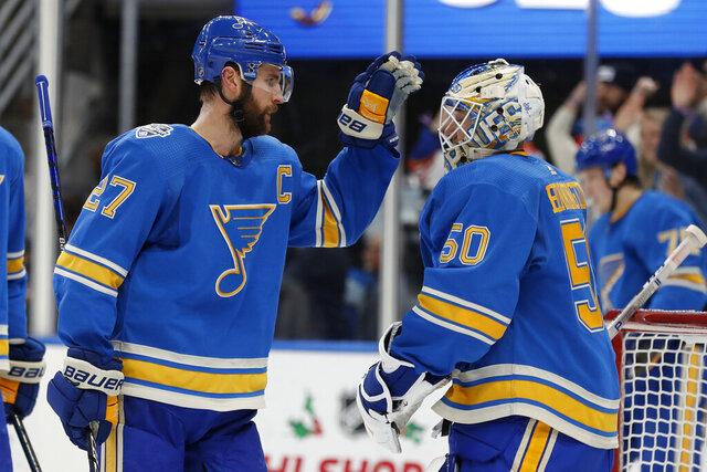 St. Louis Blues' Alex Pietrangelo, left, and goaltender Jordan Binnington celebrate a 4-3 victory over the Chicago Blackhawks in an NHL hockey game Saturday, Dec. 14, 2019, in St. Louis. (AP Photo/Jeff Roberson)